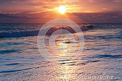 Salida del sol dramática sobre la resaca del océano