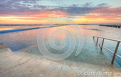 Salida del sol a partir de la una de las piscinas al océano en el Au del norte de Narrabeen
