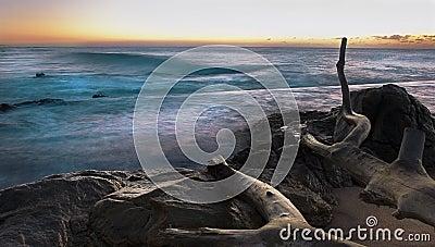 Salida del sol rocosa de la costa con la exposición larga