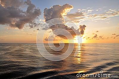 Salida del sol tropical con las nubes sobre el océano