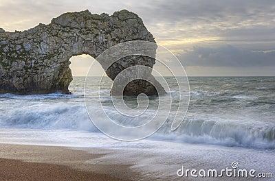 Salida del sol vibrante sobre el océano con la pila de la roca en primero plano
