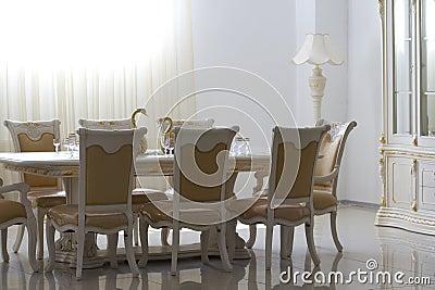 Salle à manger avec les meubles en bois blancs.