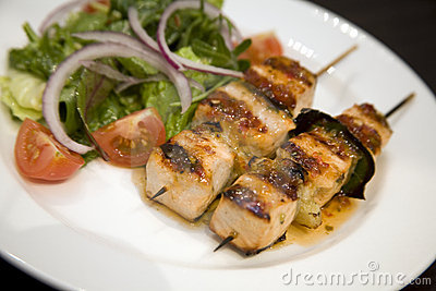 Salmon on skewers with salad