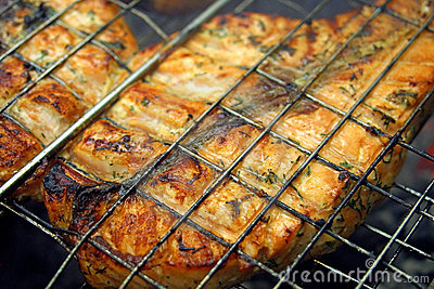 Salmon steak cooking on a grill