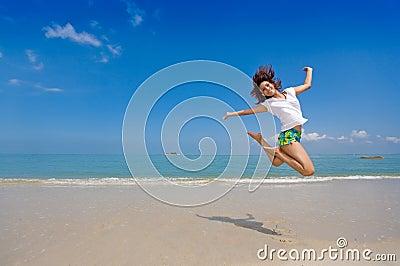 Salto felice della ragazza alla spiaggia