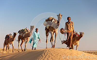 Camel man leads his camels across the Thar desert Editorial Stock Photo