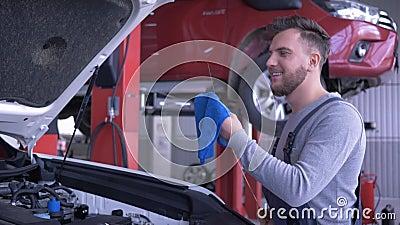 Samochód usługa, atrakcyjnych technika faceta czeków nafciany poziom podczas samochód naprawy z otwartym kapiszonem przy auto war zbiory