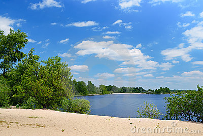 Sand beach on river with green trees