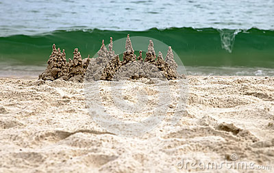 Sand castle on the beach with green wave