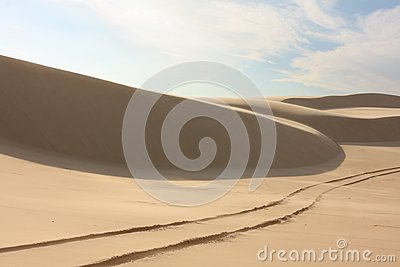 Sand dune with tyre tracks