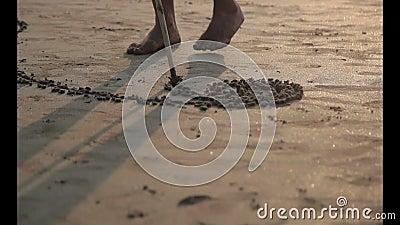 Sand painting. Man painting heart on sand art line. Arambol beach. Goa-India stock video footage