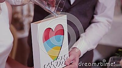 Sand-Zeremonie an der Hochzeit Bräutigam schließt das Rohr des Glasschiffes gefüllt mit Sand von verschiedenen Farben an der Hoch stock video footage