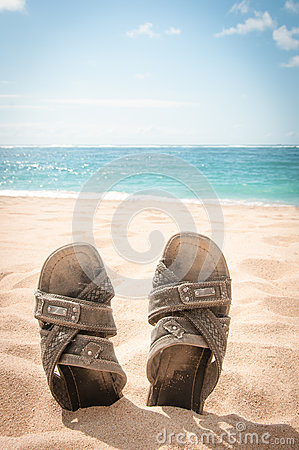 Sandals in the sand of a tropical beach