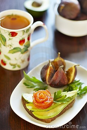 Sandwich with avocado and salmon, figs and tea