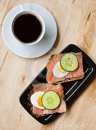 Sandwiches with rye bread and salmon and coffee