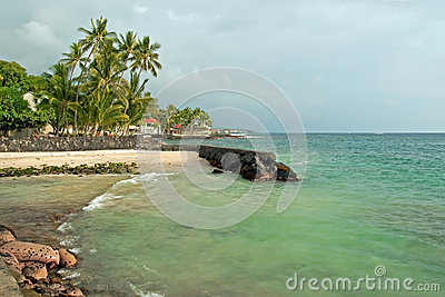 Sandy beach with azure ocean and palm trees during the storm