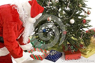 Sankt setzt Geschenke unter Baum