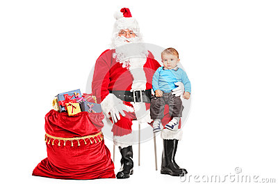 Santa and child on his lap posing next to a bag