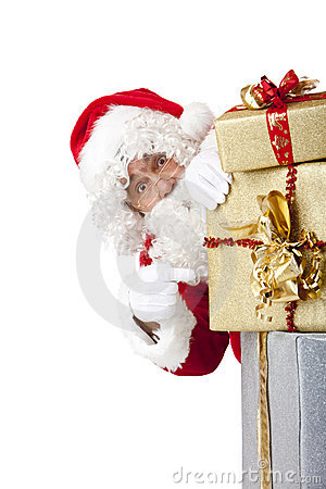 Santa Claus behind Christmas gift boxes
