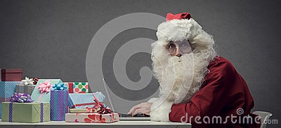 Santa Claus connecting with his laptop Stock Photo