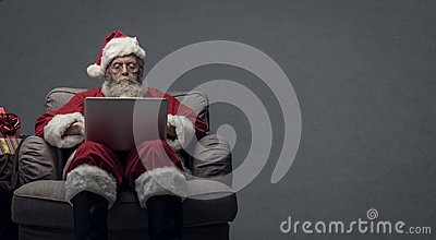 Santa Claus connecting with a laptop Stock Photo
