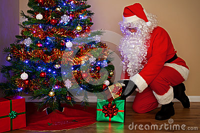 Santa Claus delivering presents under the tree.