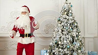 Santa Claus die moderne dans naast de Kerstboom doen stock footage