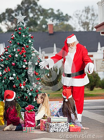 Santa Claus Gesturing At Children By Christmas