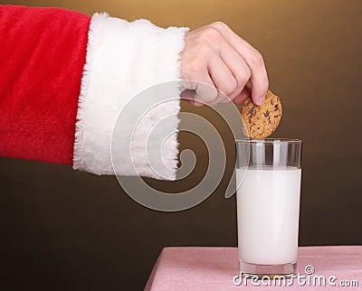Santa Claus hand holding chocolate cookie