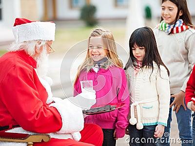 Santa Claus Offering Biscuits And Milk To Children