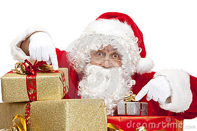 Santa Claus pointing on Christmas gift boxes