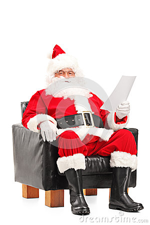 Santa Claus sitting in armchair and reading letter