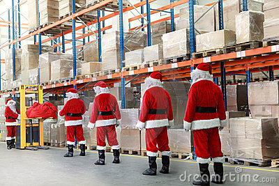 Santa clauses in the line for gifts in warehouse