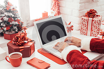 Santa connecting with a laptop Stock Photo
