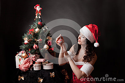 Santa girl decorates Christmas tree.