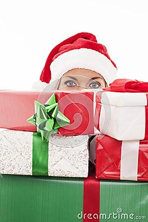 Santa girl hiding behind the gifts