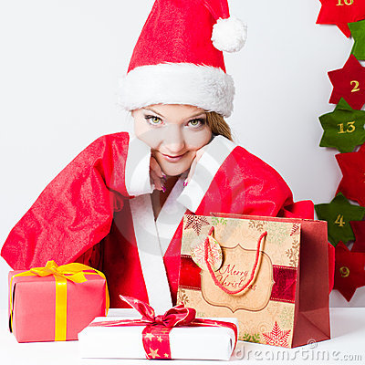 Santa girl sitting on the table with gift boxes