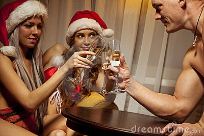 Santa girls clinking glasses of champagne with man