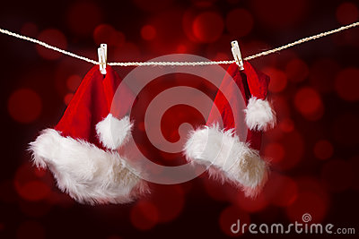 Santa hats hanging on red defocused lights