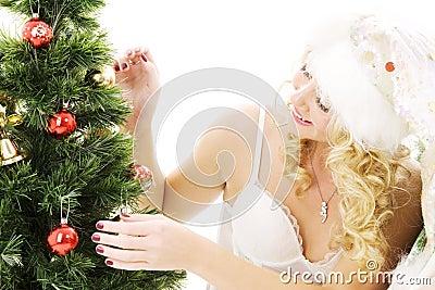 Santa helper girl decorating christmas tree