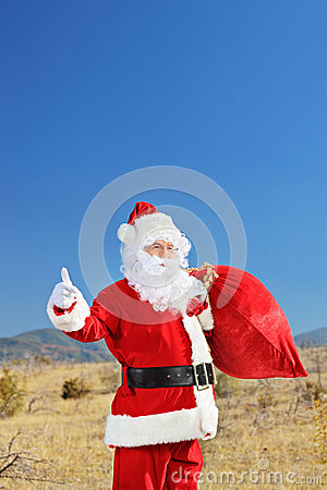 Santa hitchhiking outdoors with bag of presents
