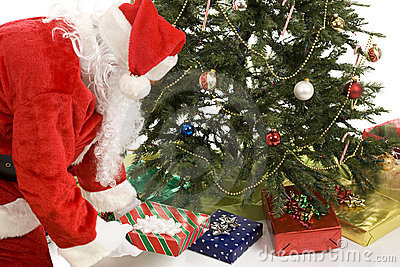 Santa pone los regalos bajo árbol