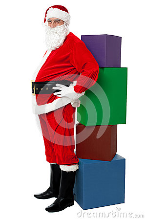 Santa standing beside pile of xmas gifts