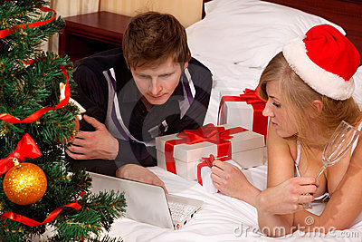 Santa woman lying on bed with her boyfriend