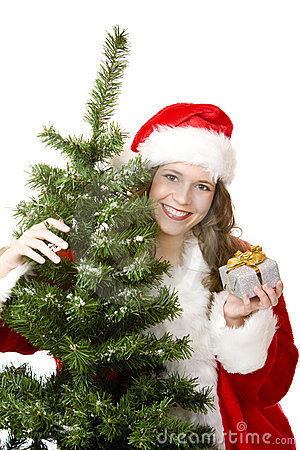 Santa Woman near fir tree holds Christmas gift