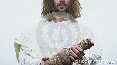 Santo en el traje blanco que alcanza hacia fuera la botella del vino, sangre de Cristo, comunión almacen de metraje de vídeo