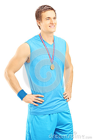 Satisfied basketball player posing with a golden medal and looki