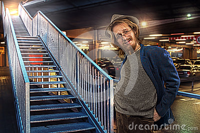 Satisfied funny man by the stairs, underground parking lot background