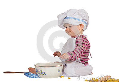 Satisfied little baby chef looking at mixing bowl