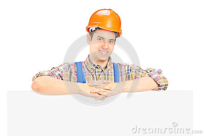 Satisfied male worker standing behind panel
